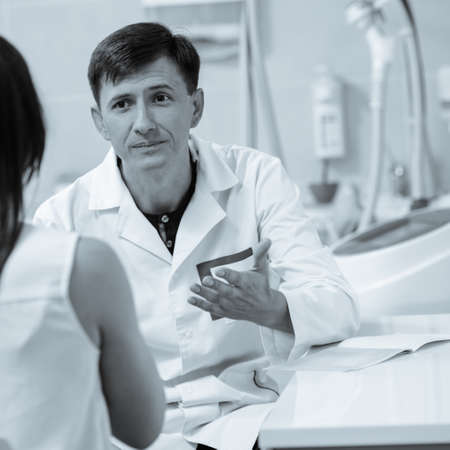 Female client talking about her skin problems with qualified beautician. black and white image with blue tint to emphasize the concept of high technology