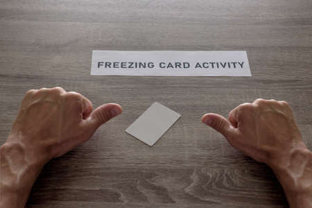 credit card and fingers points to the inscription something went wrong with finances, concept with the words freezing card activity.