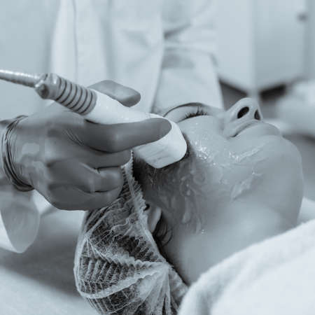 Venus Swan treatment for skin tightening and body contouring of face. black and white image with blue tint to emphasize the concept of high technology