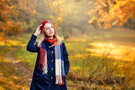Blonde happy girl in good mood posing in autumn park, walks for a womans peace of mind
