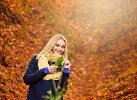 Portrait of beautiful happy young girl wearing warm scarf in autumn forest, walks for a womans peace of mind