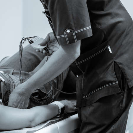Dnepr, Ukraine- July 17, 2020: Male therapist positioning electrodes on patients body for electro stimblation procedure. black and white image with blue tint to emphasize Redactioneel