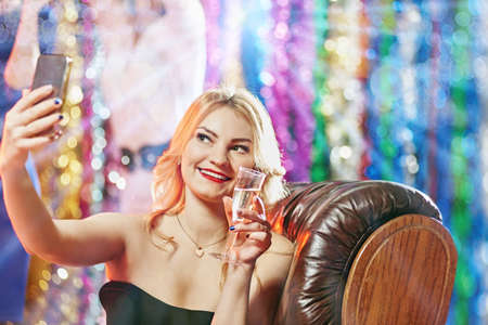 Pretty glamour blonde having party and making selfie with glass of champagne Stok Fotoğraf