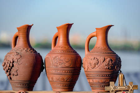 Different traditional Ukrainian pottery pots with ornament in souvenir shop, products of forming vessels and other objects with clay and other ceramic materials