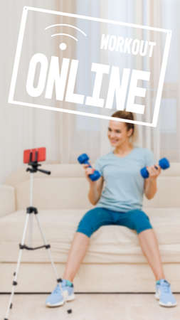Young female fitness trainer with dumbbells recording video blog, work as a trainer from home online remote, image with text workout online and oriented for use on a smartphone. 写真素材