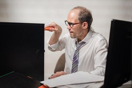 Upset office worker trying to fix his broken computer