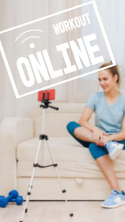 Attractive positive woman recording video for watching tutorial lesson at home, Communication through instant messengers, image with text workout online and oriented for use on a smartphone. 写真素材