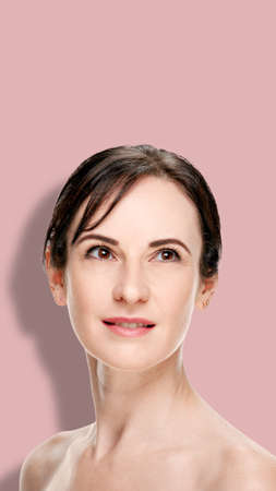 Brunette woman with natural makeup and clean skin on pink background, image oriented for smartphone