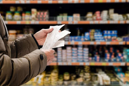 Minded man viewing receipts in supermarket and tracking prices Stock fotó