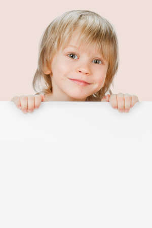 Little smiling child holding empty white poster