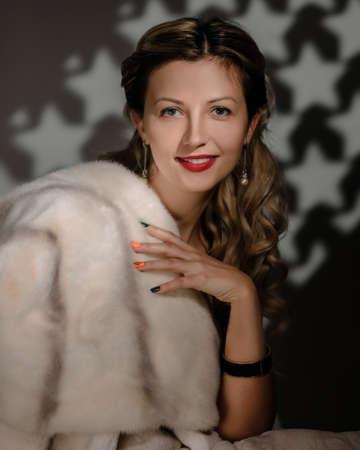 Fashion portrait of gorgeous blonde woman posing in white fur coat Archivio Fotografico