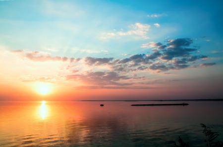 湖の表面の上の劇的な美しい夕焼け曇り空