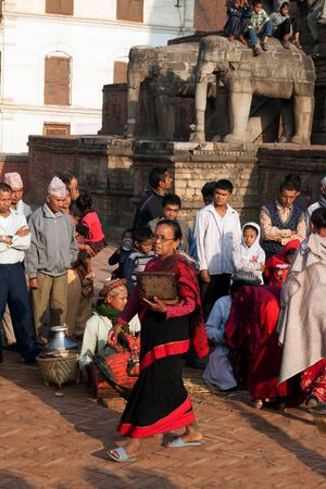 incubus: BHAKTAPUR NEPAL APRIL 19 2013: Nepalese women Newars make a religious ritual puja offering sculptural image of the deity of food water incense flowers. Bisket Jatra is which is held during the celebration of Nepali New Year on the square in Bhaktapur.