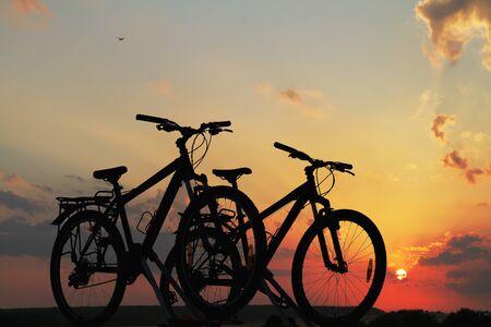 Bici sul tetto di una macchina contro il tramonto.