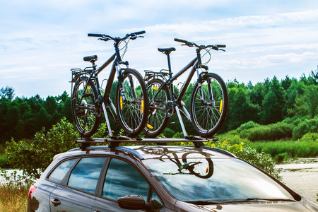 Bikes on top of a car near a forest lake.