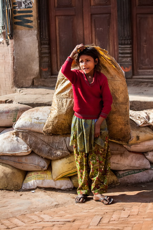 poorly: BHAKTAPUR, NEPAL - APRIL 19, 2013: Child Labour in Asia. Poorly dressed teen girl drags the heavy bags on the square in Bhaktapur.