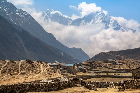 icefall: Mountain village under the snow-capped peaks in Gokio Valley. Nepal. Himalayas.
