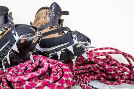 crampon: Old professional climbing gear. Rope, ice screws, crampon  hobnailed boots on. Stock Photo