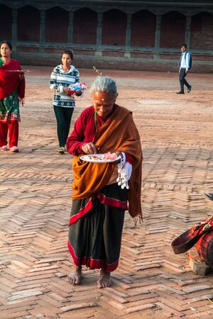 incubus: BHAKTAPUR, NEPAL - APRIL 19, 2013:Elderly woman - Newar hurry to make a religious ritual puja - offering sculptural image of the deity of food, water, incense, flowers . Bisket Jatra is  which is held during the celebration of Nepali New Year on the squar Editorial