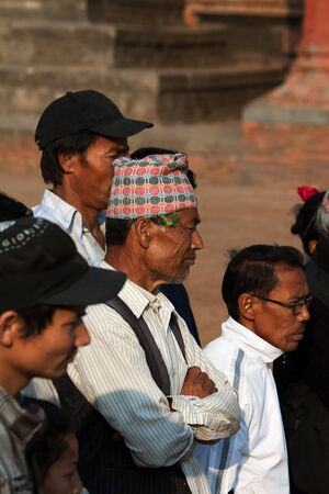 incubus: BHAKTAPUR, NEPAL - APRIL 19, 2013:Men  of Bhaktapur in the national headdress -Dhaka Topi is participants and spectators watch a ritual dance called Bhairav Dance in Bisket Jatra is  which is held during the celebration of Nepali New Year on the square in
