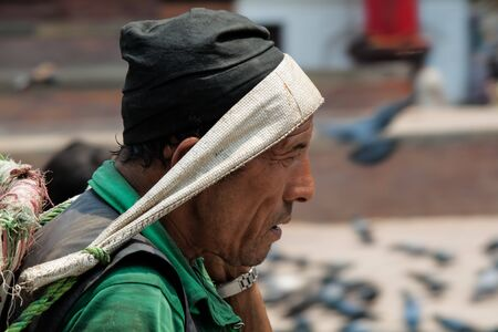 carrying heavy: KATMANDU, NEPAL -  APRIL 15 2013: Nepali man with a basket for carrying heavy loads on their heads.