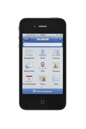 demonstrated: Münster, Germany - February 27, 2011: Facebook Inc.s mobile application demonstrated on an Apple Inc. iPhone isolated on a white background.