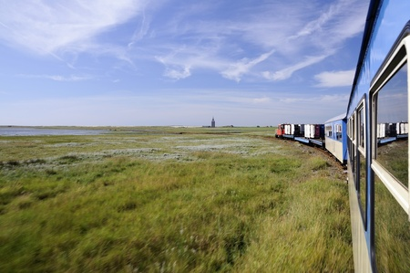 A little old island train connects harbour and village on Wangerooge, Germany. Stock Photo