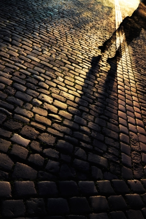 Walking on a cobbled street at night Stock Photo