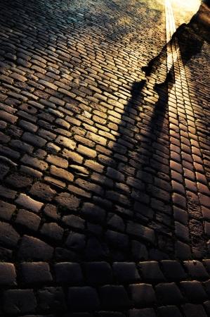 Walking on a cobbled street at night Standard-Bild