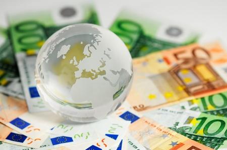 capitalismo: Globo de cristal y variedad de billetes dispararon sobre un fondo blanco