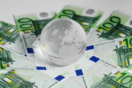 Glass globe and 100 euro bundle set on white background  photo