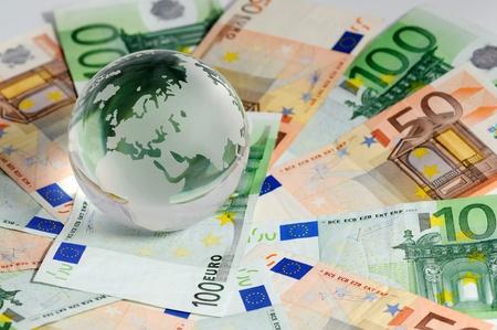 Glas-Globe und Vielzahl von Banknoten erschossen auf weißem Hintergrund  Standard-Bild - 9586743
