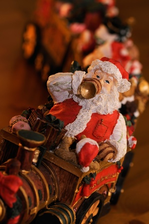 Beautiful wooden Santa figurine sitting on train  photo