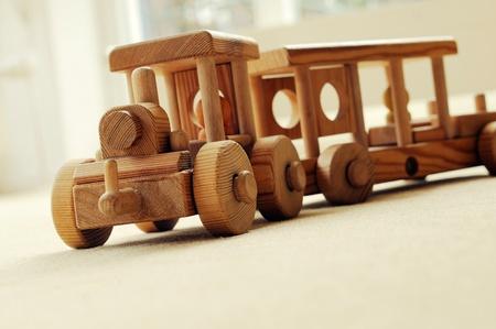 Met de hand gemaakte houten trein op een beige tapijt.