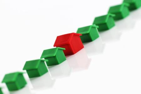 monopolio: Muenster, Alemania - el 10 de abril de 2010: Fila de casas de pl�sticas rojas y verdes de la famosa propiedad comercial juego de mesa Monopoly, aislado en blanco. Monopolio pertenece y es fabricado por Hasbro.