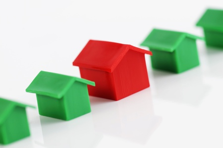 Muenster, Germany - April 10, 2010: Row of red and green plastic houses from the famous property trading board game Monopoly, isolated on white. Monopoly is owned and manufactured by Hasbro.