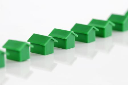 monopolio: Muenster, Alemania - el 10 de abril de 2010: Fila de casas de pl�sticos verdes de la famosa propiedad comercial juego de mesa Monopoly, aislado en blanco. Monopolio pertenece y es fabricado por Hasbro.