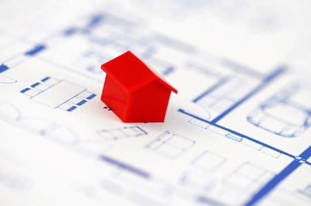 monopolio: Muenster, Alemania - el 10 de abril de 2010: Primer plano de una casa modelo rojo desde la propiedad famosa juego de mesa Monopoly, con plan de arquitectura de comercio. Monopolio pertenece y es fabricado por Hasbro.