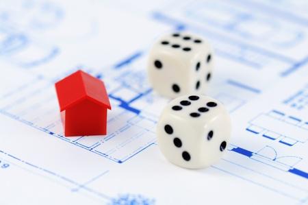 monopolio: Muenster, Alemania - el 10 de abril de 2010: Primer plano de una casa modelo rojo de la famosa propiedad comercial juego de mesa Monopoly, con plan de arquitectura y dos dados con valor de 6. Monopolio pertenece y es fabricado por Hasbro.