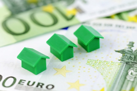 Muenster, Germany - April 10, 2010: Close-up of green model houses from the famous property trading board game Monopoly, with hundred euro banknotes. Monopoly is owned and manufactured by Hasbro.