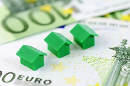 monopolio: Muenster, Alemania - el 10 de abril de 2010: Primer plano de Casas modelo verde de la propiedad famosa juego de mesa Monopoly, con cientos de billetes de comercio. Monopolio pertenece y es fabricado por Hasbro.