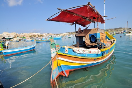 trawler net: Traditional Maltese fishing boats, called Luzzu, in the harbour of Marsaxlokk, Malta.  Editorial
