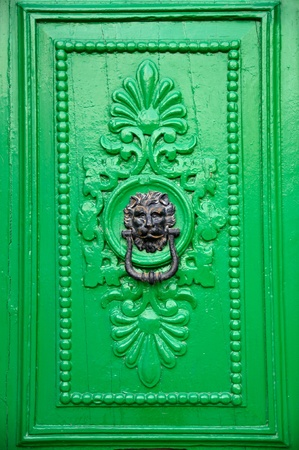 Black lion head door knocker on green door in Valletta, Malta.  photo