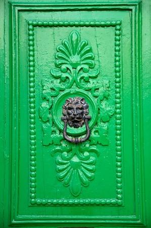 wood carving door: Black lion head door knocker on green door in Valletta, Malta.