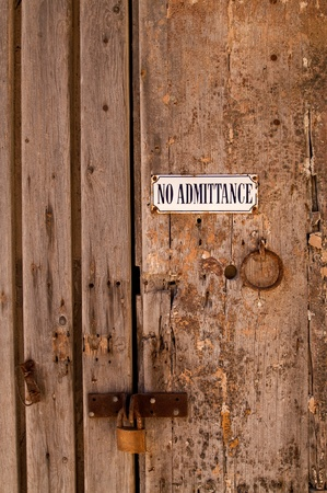 entrance sign: Grunge No Admittance sign on old wooden door locked with padlock in Mdina, Malta