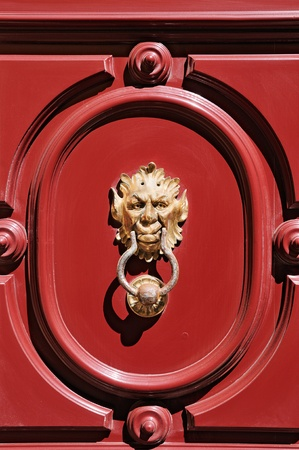 Gargoyle head door knocker on red door in Mdina, Malta.  photo