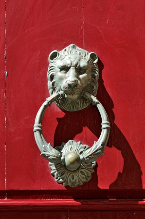 view of a wooden doorway: Bronze lion door knocker on red door in Mdina, Malta.  Stock Photo