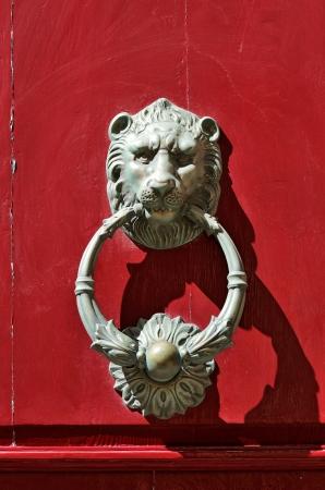 cerrar la puerta: Le�n de bronce aldaba en la puerta roja en Mdina, Malta. Foto de archivo