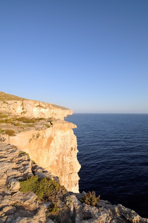 steep cliff: The Cliffs of Mtahleb with Filfla Island showing on the horizon Stock Photo