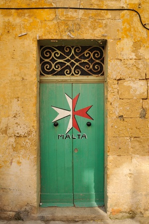 view of a wooden doorway: Maltese Cross painted on a old green doorway, Malta.